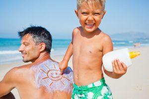 Sohne cremt Vater mit Sonnenmilch ein