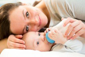 Mutter füttert Baby mit Flasche